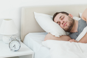 man sleeping soundly in bed with a lamp and alarm clock on his nightstand