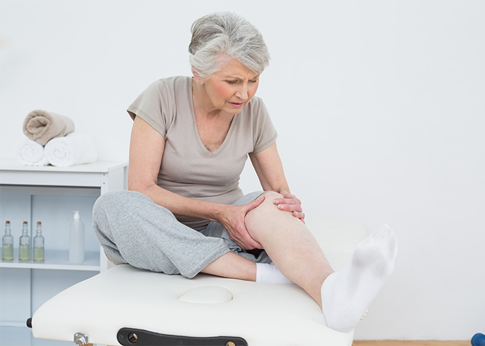 senior woman struggling with joint pain in her knees