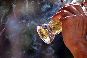 close up on a man's hand holding a glass of beer and lit cigarette