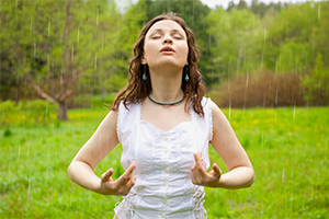 woman doing breathing exercises outdoors in a park
