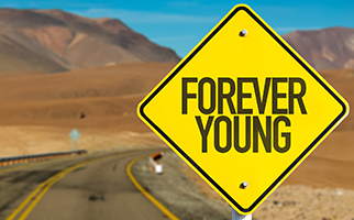 "yellow signboard on a deserted road with the words ""forever young"""