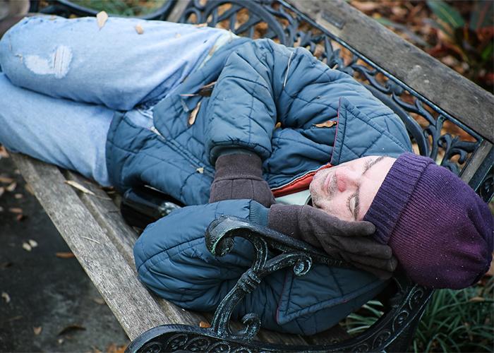 Homeless man asleep on a park bench