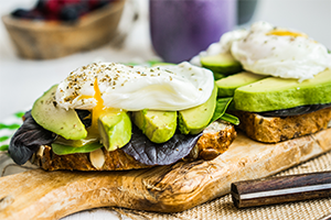 two slices of toasts topped with salad greens, avocado, and poached eggs