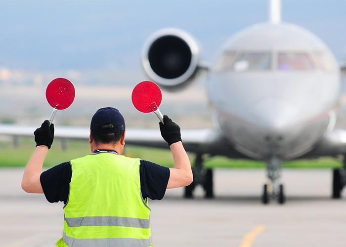 air traffic controller waving a plane in
