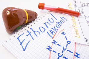 human liver next to a vial of blood and a notepad page with alcohol and molecular structure of ethanol written in marker