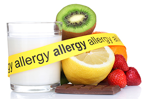 """glass of milk, kiwi, lemon, chocolate, orange, and strawberries with a yellow tape across them saying """"allergy"""""""