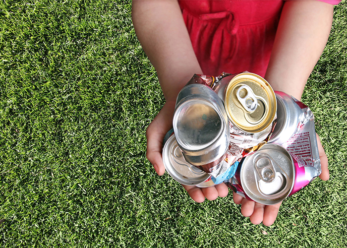 child holding crushed aluminum cans