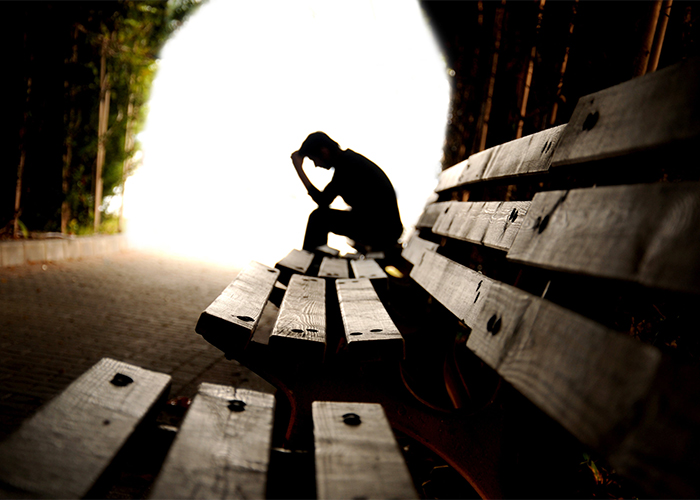 silhouette of a stressed out male sitting on a bench