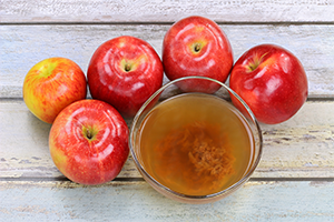 apple cider vinegar with mother in a glass bowl with fresh red apples around it