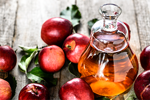 jar of apple cider vinegar with fresh red apples around it on a wooden table