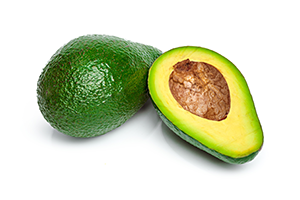 a whole avocado and a halved avocado on a white surface