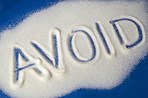 "the word ""avoid"" spelt out in sugar scattered on a blue table"