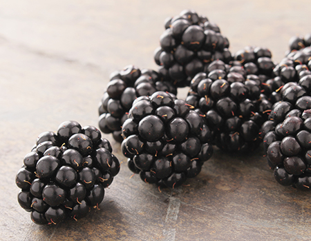 close up of blackberries on a wooden table