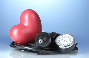 a plastic heart lying on top of a blood pressure pump