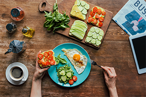 top down shot of someone having a healthy breakfast of eggs, veggie on toast, and coffee