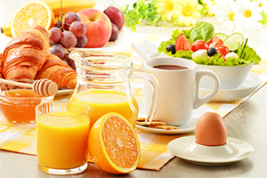 a breakfast table with salad, fresh juice, eggs, fruits, croissants, and a cup of coffee