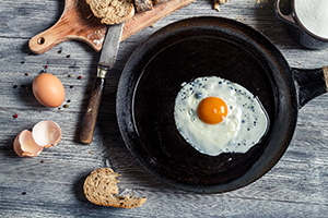fried egg in an iron pan on a wooden table with broken egg shells and pieces of bread next to it