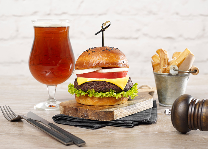 burger, beer, and fries with gluten on a table