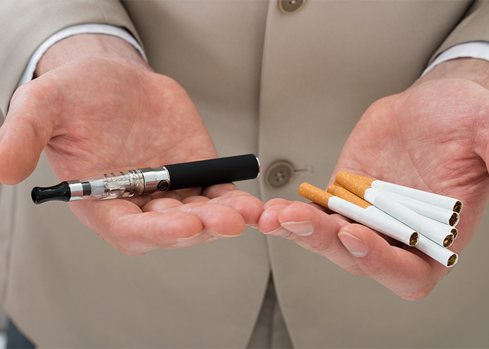 man holding electronic cigarette and tobacco cigarettes