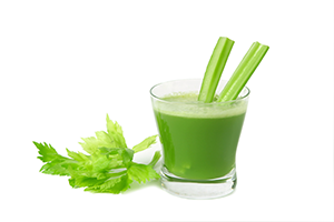 a glass of green celery juice with a couple of stalks in the glass and celery leaves by the side