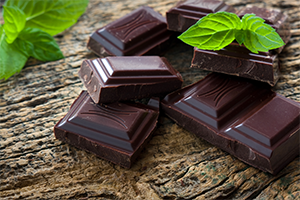 pieces of dark chocolate on a wooden table with mint leaves around