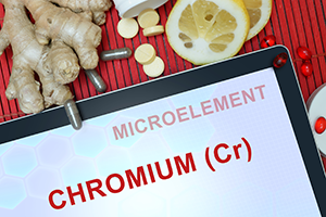 an ipad with the words chromium in bright red on a table, and ginger, lemon slices and supplement pills scattered around it