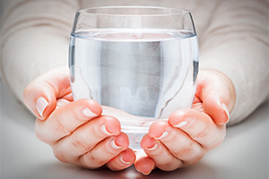 woman holding a glass of clean water in two hands