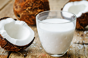 glass of coconut milk with fresh coconuts around it