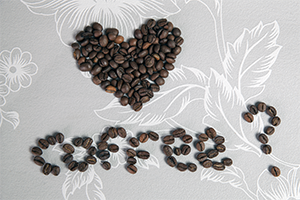 coffee beans spelling out the word coffee with the shape of a heart above it