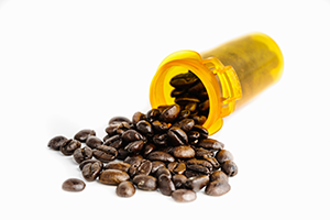 coffee beans coming out of a pill bottle