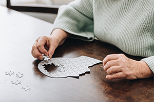 closeup of elderly woman's hands putting pieces of a puzzle of a human head together