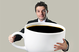 man in a suit holding a massive cup of coffee