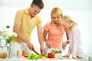 a father, mother, and child preparing a fresh salad in the kitchen
