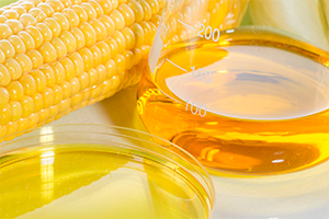 corn syrup in a beaker with a cob of corn in the background