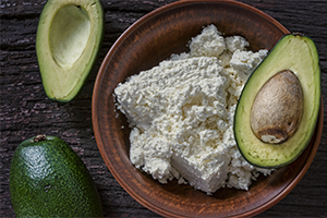 cottage cheese and avocado on a brown earthenware plate