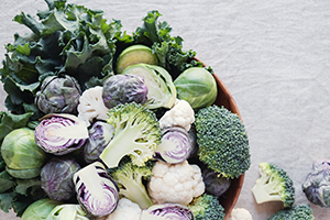 different types of cruciferous vegetables such as broccoli and kale in a wooden bowl