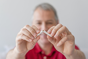 middle aged man breaking a cigarette in half