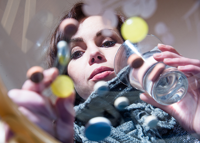 young woman sorting through her pills
