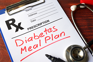 clipboard with prescription pad and red letters spelling out diabetes meal plan