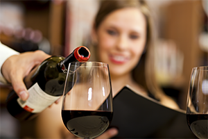 close up of waiter pouring red wine into a glass