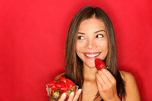 woman holding up fresh strawberries and smiling