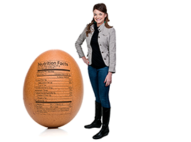 woman standing next to oversized egg with nutrition facts on it