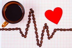 topdown view of electrocardiogram line made with roasted coffee grains with a cup of coffee and a red paper heart