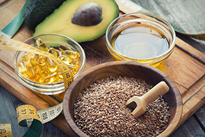 shot of healthy foods like omega-3 supplement pills, avocado and brown grains on a wooden board