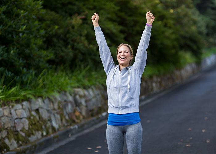woman exercising and celebrating outside
