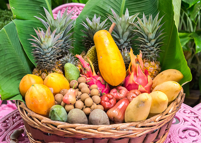 basket of tropical fruit including pineapple, mango, and papaya