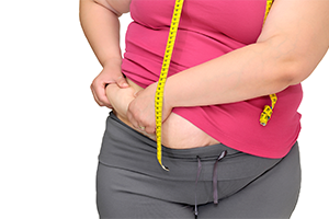 overweight woman with a tape measure around her neck grabbing her love handles