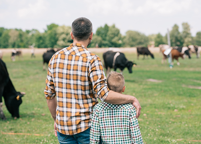 father and son standing together and looking at cows grazing on farm