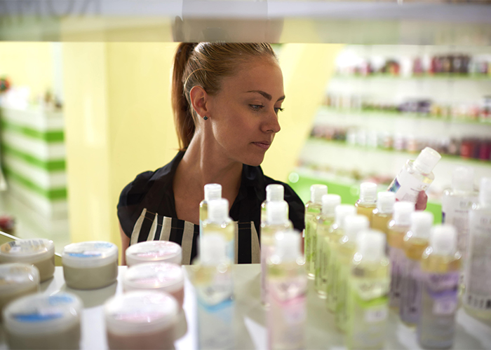 female consultant looks cosmetic products in plastic packaging