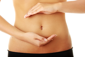 fit young woman's belly with her hands framing her abdominal area